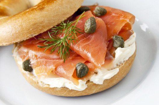 Sie können die Bagel klassisch mit Frischkäse bestreichen und mit Räucherlachs belegen. (Bild: mipstudio – shutterstock.com)
