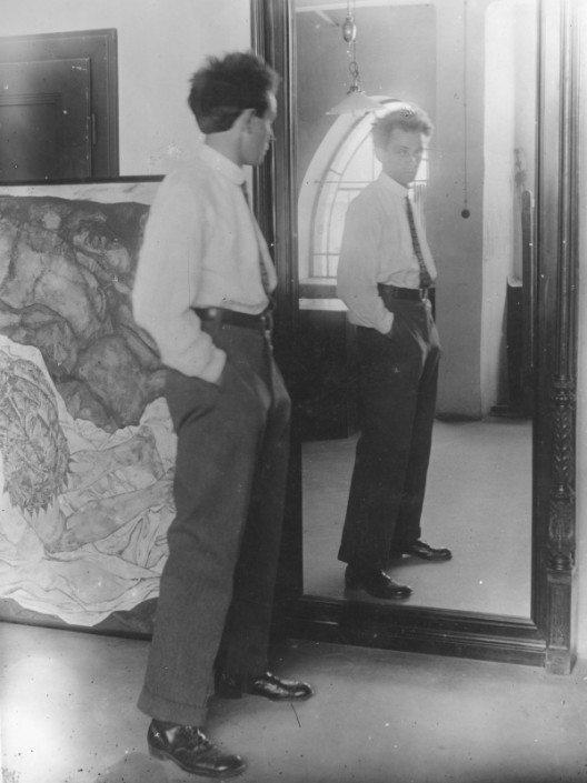 Porträt von Egon Schiele aus dem Jahr 1915 vor seinem Spiegel im Hietzinger Atelier, im Hintergrund das Gemälde »Tod und Mädchen«, Fotografie von Johannes Fischer © Leopold Privatsammlung/Foto: Leopold Museum, Wien