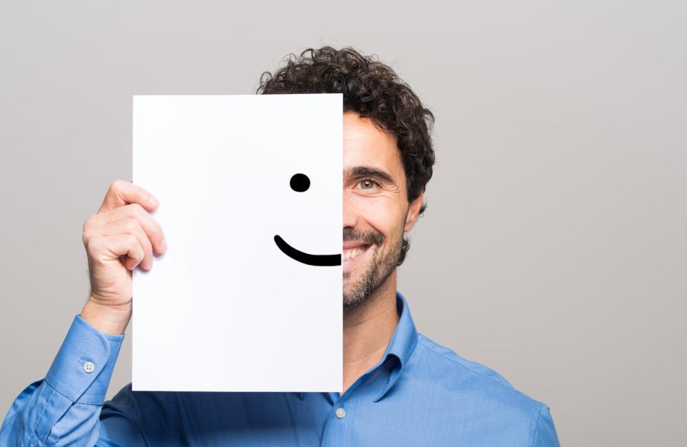 Happy Mann, der sein halbes Gesicht mit einem lächelnden Emoticon bedeckt