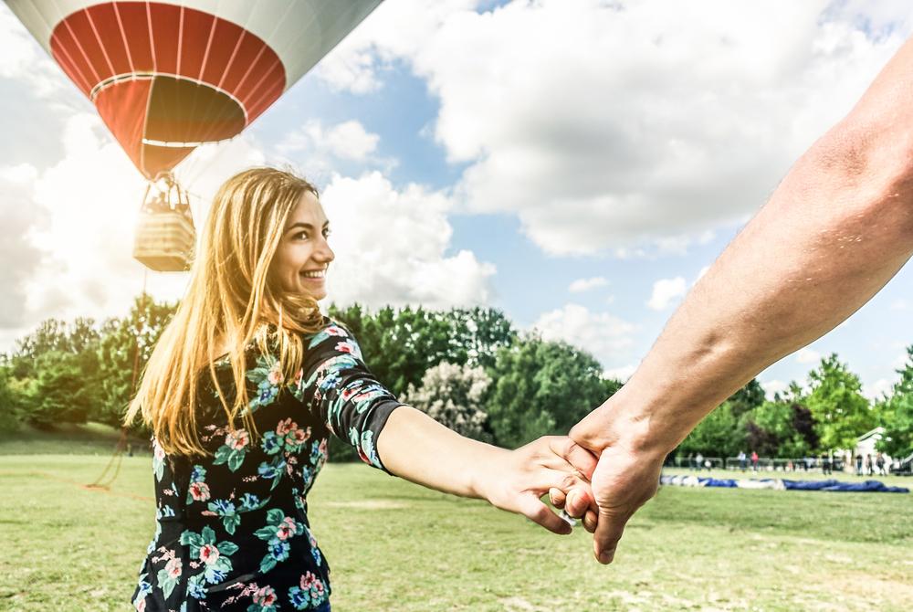 Fröhliche junge Frau will Ballontournee mit der Hand eines Freundes machen